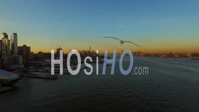 Nyc New York Usa Flying Low Over Hudson River Panning Left With Jersey City And Manhattan Cityscape Views At Sunrise - Drone Point Of View