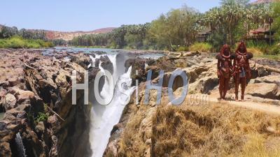Vue Aérienne De Deux Femmes De La Tribu Himba Devant Des Cascades D'epupa à La Frontière Entre L'angola Et La Namibie, En Afriqu - Vu Par Drone
