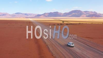 Aerial View Over A Safari Vehicle Heading Across The Flat, Barren Namib Desert In Namibia - Drone Point Of View