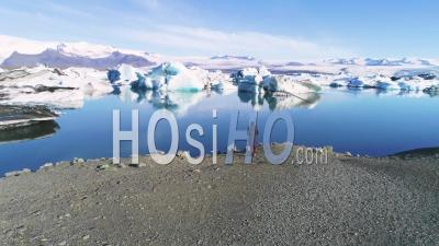 Aerial View Of A Woman Standing Along The Shore Of A Glacier Lagoon, In The Arctic At Jokulsarlon Glacier Lagoon, Iceland - Drone Point Of View
