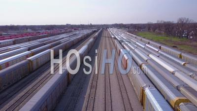 Aerial View Over A Railroad Yard Suggests Shipping, Commerce, Trade Or Logistics - Video Drone Footage