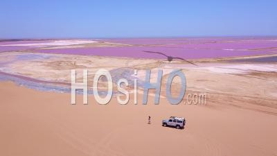Vue Aérienne Sur Une Femme Faisant Du Jogging Ou Courant Sur Une Région Colorée De Sel Rose En Namibie, Afrique - Vidéo Drone