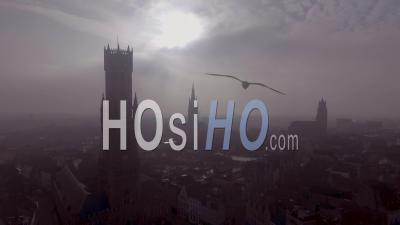 Aerial View Of A Mysterious Foggy Day Of Bruges, Belgium With Cathedral Churches And Spires In Distance - Video Drone Footage