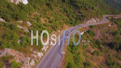Aerial View Over Three People Riding Mopeds Or Vespa Scooters Along A Two Land Mountain Road In Croatia - Video Drone Footage