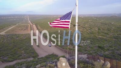 Le Drapeau Américain Flotte Au-Dessus De La Frontière Entre Les États-Unis Et Le Mexique Dans Le Désert De Californie Alors Qu'un Véhicule De Patrouille De La Frontière Passe Au-Dessous