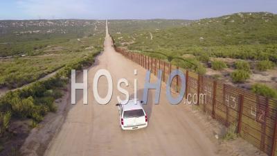 Vue Aérienne Sur Un Véhicule De Patrouille Frontalière Debout Garde Près Du Mur Frontière à La Frontière Américaine Du Mexique - Vidéo Drone