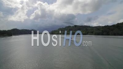 A Motorboat Travels On The Rio Dulce River In Guatemala - Drone Point Of View