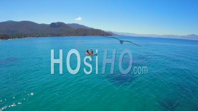 Vue Aérienne D'un Couple Assis Sur Un Planche Paddle Au Lac Tahoe - Vidéo Drone