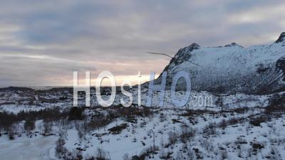 Sunset Behind Snowy Mountain In The Lofoten Islands - Video Drone Footage