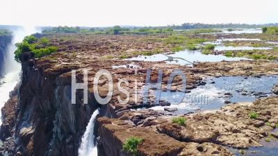 Vue Aérienne D'un Homme Et D'une Femme Assis Dans La Cascade De La Piscine Du Diable à Victoria Falls En Zambie - Vidéo Drone