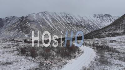 Frozen Landscape During A Foggy Day, Road In First Row And Mountains In The Background - Video Drone Footage