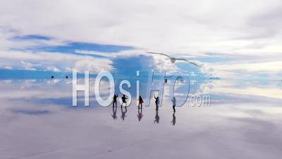 Aerial View Of Silhouetted People Dancing On The Uyuni Salt Flats Lake With Perfect Reflections In Bolivia - Video Drone Footage