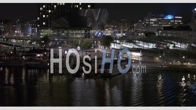 Ferry Docking At Klara Malarstrand At Night With Stockholm Centralstation In Background, Sweden - Video Drone Footage