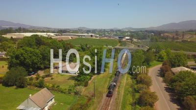 Steam Train Arriving At Rural Train Station - Drone Point Of View