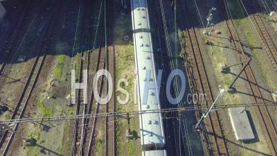 Passenger Train Under Bridge At Major Station - Video Drone Footage