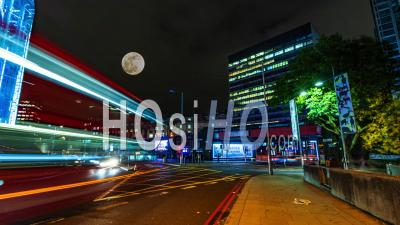 A Busy Crossroad Near Waterloo Station In London At Night With Full Moon