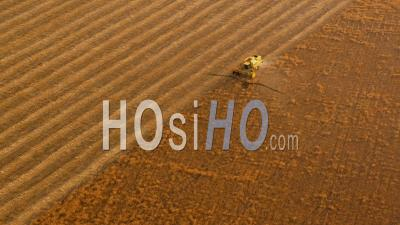 Aerial View Of (wide Shot) Combine Harvester Working In Wheat Field