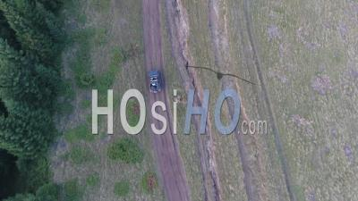 Off-Road Car Driving On A Mountain Dirt Road - Drone Point Of View