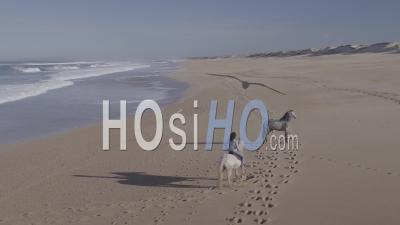 Horse Rider Woman And A Second Horse Waiting On A Deserted Beach - Aerial Video By Drone