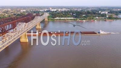 River Barge Under Three Steel Bridges Over The Mississippi River With Memphis, Tennessee Background - Aerial Video By Drone