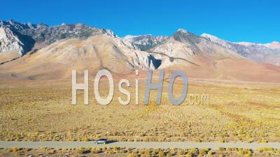 Aerial Of A 4wd Wheel Drive Vehicle On A Road In Front Of The Eastern Sierras With Mt. Whitney In Ther Distance Suggesting Remote Road Trip Adventure. - Drone Point Of View