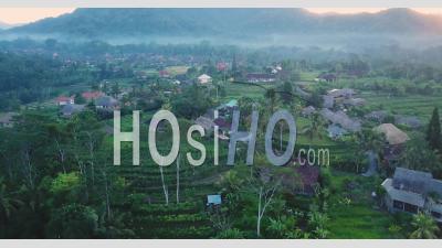 Village Agricole Indonésien Dans Un Matin Enfumé Avec Un Ciel Rose - Vidéo Aérienne Par Drone