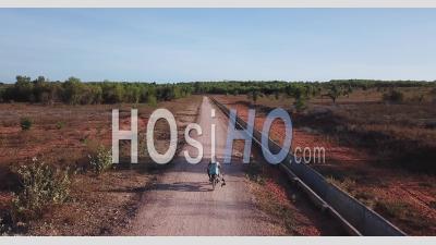 Moto Sur Une Route De Campagne Déserte Et Poussiéreuse De Sable Rouge - Vidéo Drone