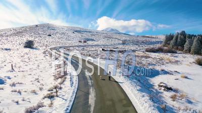 2020 - Vue Aérienne D'une Femme Autorisée Chien Qui Marche Le Long De La Route De Montagne Couverte De Neige Dans L'est De La Sierra Nevada Près De Mammoth Lakes En Californie. - Vidéo Par Drone