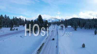 2020 - Vue Aérienne De Voitures Roulant Lentement Sur La Route De Montagne Couverte De Neige Glacée Dans Les Montagnes De L'est De La Sierra Nevada Près De Mammoth En Californie - Vidéo Par Drone