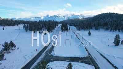 2020 - Aerial Of Cars Driving Slowly On Icy Snow Covered Mountain Road In The Eastern Sierra Nevada Mountains Near Mammoth California. - Video Drone Footage