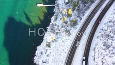 2020 - Top Down Aerial Pov Of A Car Traveling On A Snowy Road Through A Tunnel Beside A Lake. - Video Drone Footage