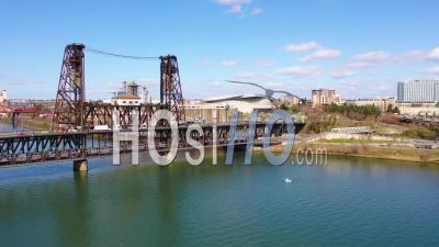 Belle Vue Aérienne D'amtrak Passenger Train Crossing Bridge Et En Arrivant à Portland, Oregon, Avec Light Rail Au-Dessus Et Moda Center Background -  Vidéo Par Drone