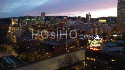 Night Aerial Past Portland Oregon Stag Deer Sign And Downtown Old Town Cityscape And Business District. - Video Drone Footage