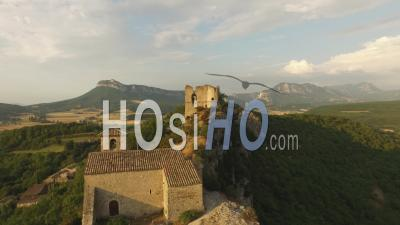Église Et Un Château En Ruines Au Sommet D'une Falaise Sur Un Petit Village, France - Vidéo Drone