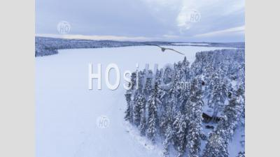 Snow Covered Lake And Forest Winter Landscape Showing Amazing Lapland Scenery In Scandinavia In Finland Drone