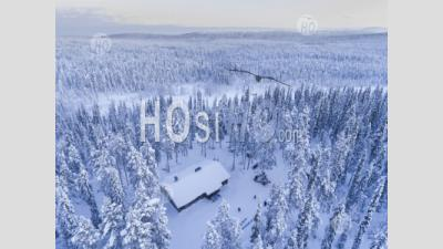 Aerial Photo Of A Cabin In A Snow Covered Winter Forest Of Trees At Sunset In The Arctic Circle In Finnish Lapland, Finland - Aerial Photography