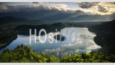 Timelapse De Paysage De Montagne Au Lever Du Soleil Avec La Lumière Du Soleil Frappant Le Lac De L'île De Bled En Slovénie. Laps De Temps Des Nuages Se Formant Sur La Chaîne Des Montagnes Des Alpes Juliennes