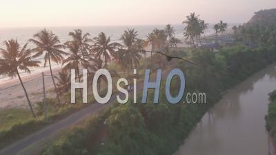 A Motorcycle Crossing A Small Concrete Road Next To The Varkala Beach Under The Sunset In Kerala, India - Aerial Drone Shot