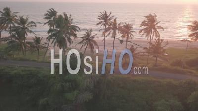A Single Vehicle On The Road Beside The Coastline Of Varkala Beach In The State Of Kerala, India - Aerial Drone Shot
