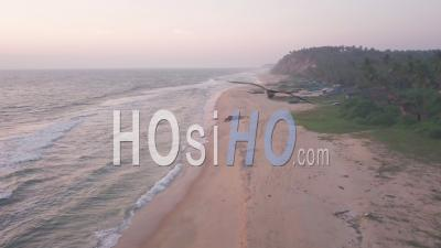 Aerial Drone View Of Varkala Coastline With Waves Crashing On The Sandy Beach, In Kerala, India, At Dusk