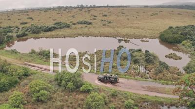 4 Wheel Drive Vehicle Driving Through Muddy Puddle In Aberdare National Park, Kenya, Africa. Aerial Drone View