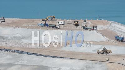 Trucks Working On Landfill Area In Kowloon, Hong Kong On A Sunny Day.- Wide Shot