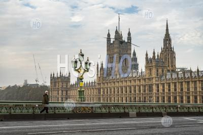 London In Coronavirus Covid-19 Lockdown, Quiet With Empty Roads And Streets With Almost No People, Just One Person Commuting, With Houses Of Parliament In England, Uk At Rush Hour