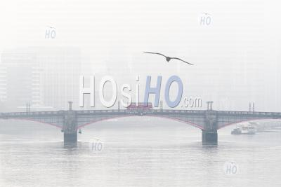 Central London City Skyline With Iconic Red London Bus Driving Over Lambeth Bridge With Misty Foggy Skyscraper Buildings Shot In Coronavirus Covid-19 Lockdown In England, Uk