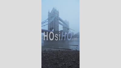 Vidéo Verticale Du Tower Bridge Et De La Tamise Beach à Marée Basse, Montrant L'emblématique Monument De Londres Dans Le Brouillard Et Le Temps Brumeux Dans Le Brouillard Et Le Brouillard Dans Le Coronavirus Covid-19 Lockdown, England, Uk