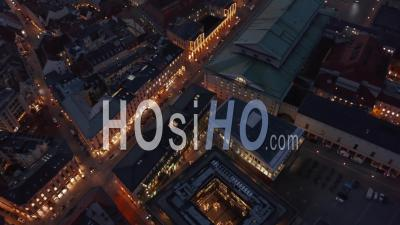 Scenic Aerial View Passing Through Munich, Germany Neighborhood Street At Night With Beautiful City Lights Glowing And Cars Passing By, Aerial Tilt Down High Angle - Video Drone Footage