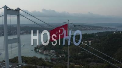 Turkish Flag Waving In Wind In Front Of Istanbul Bosphorus Bridge, Aerial Medium Shot Slide Right - Video Drone Footage