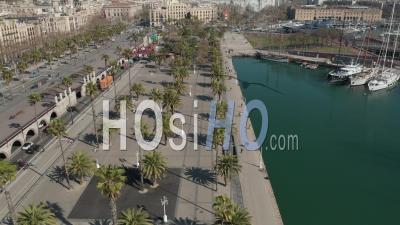 Aerial Slow Flight Along The Docks With Busy Street On The Left And Boats In Water In Barcelona, Spain With Palm Trees On Beautiful Sunny Day 4k - Video Drone Footage