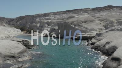 Aerial Flight Through Beautiful Sarakiniko Lunar Volcanic Beach Canyon With Tourists In Water In Milos Island, Greece 4k - Video Drone Footage