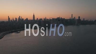 Over East River Overlooking Manhattan New York City Skyline In Beautiful Dawn Sunset Orange Light 4k - Video Drone Footage